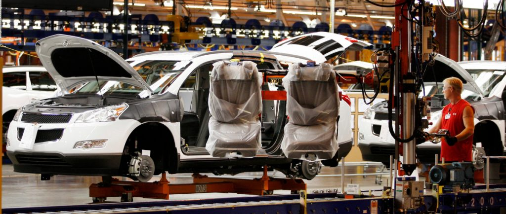 Assembly line worker Melvin Matthews uses a large robotic machine to install front seats in a new 2009 Chevrolet Traverse at the GM manufacturing plant in Spring Hill, Tenn.