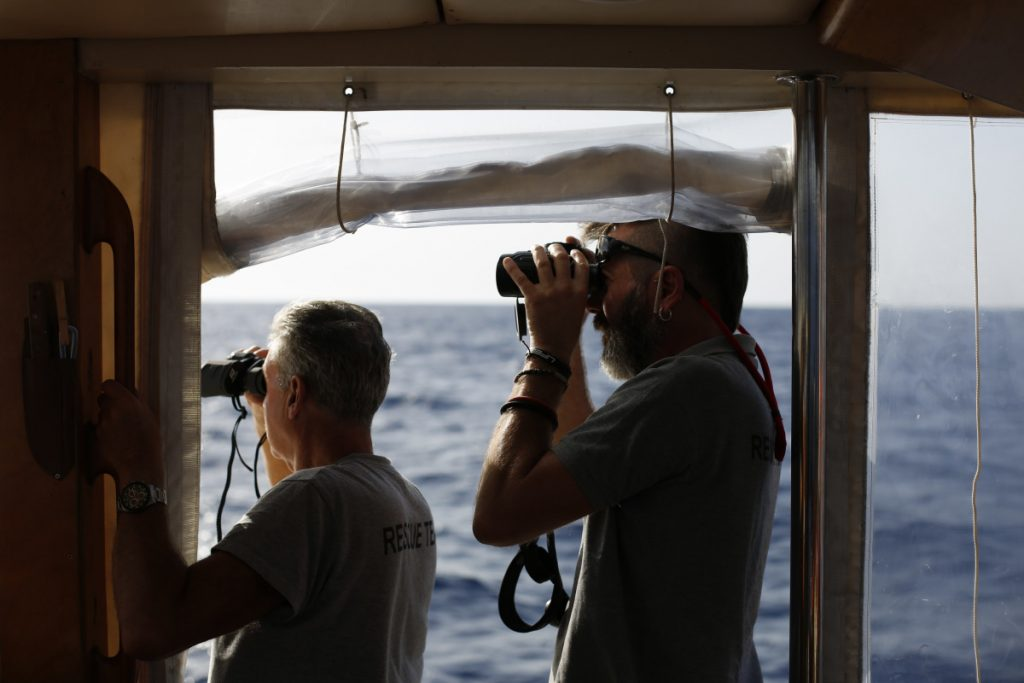 Spanish NGO Proactiva Open Arms captain Riccardo Gatti, right, and volunteer Victor Aguinaga look at the horizon with binoculars in search of migrants in the Mediterranean Sea.