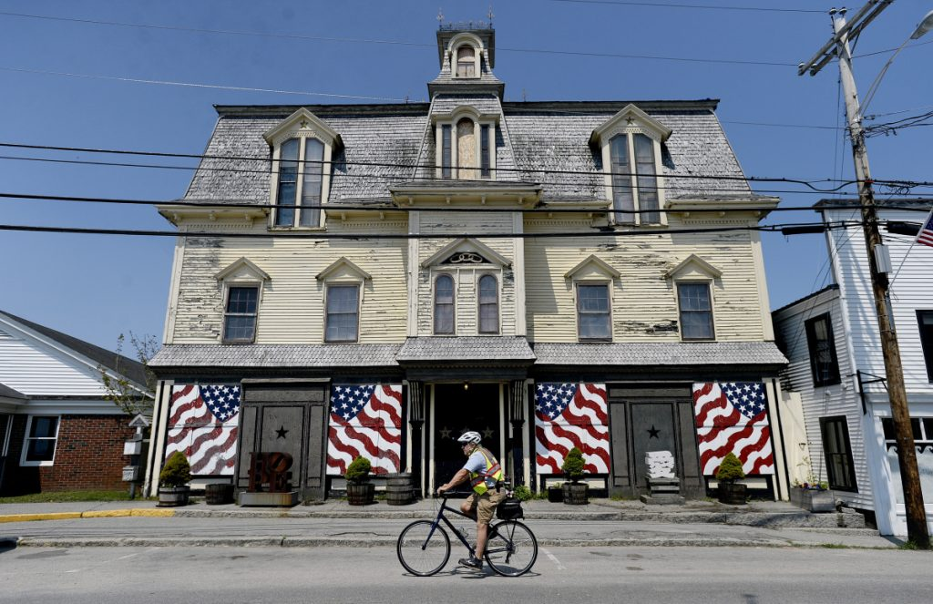 Vinalhaven resident Chuck Clapham rides past Robert Indiana's home on the Penobcot Bay island, a former Odd Fellows hall called Star of Hope. An attorney for Indiana will meet with others on Aug. 15 for a hearing on 28 pieces of art missing from the home. Those artworks are listed in exhibition catalogs as belonging to Indiana, but weren't found in Star of Hope. Staff photo by Shawn Patrick Ouellette