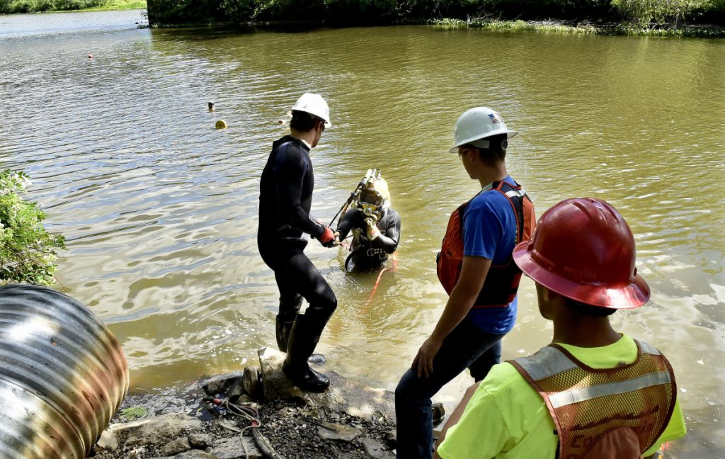 Hard-hat diver Kenny Strout, center, of Commercial Divers Inc., is handed tools to make repairs Tuesday to a 16-inch water line in Messalonskee Stream off North Riverside Drive in Waterville. The line broke Monday, stirring up sediment in the pipes and causing discoloration in the water, which nevertheless is safe to drink and use, according to the Kennebec Water District.