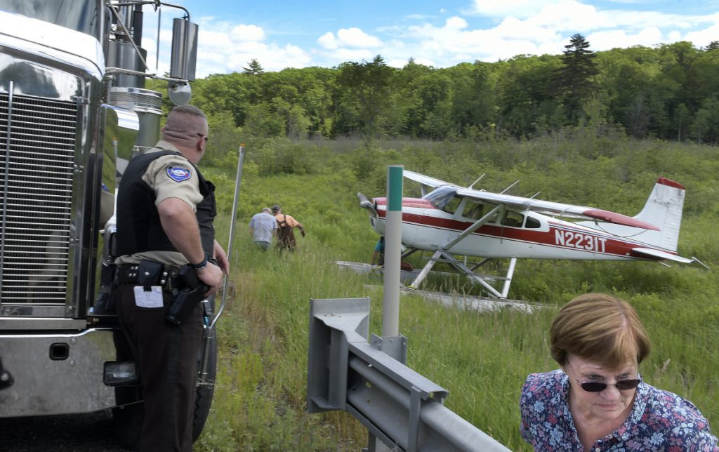 Folks watch a single prop airplane get towed Sunday to Route 126 in Jefferson.