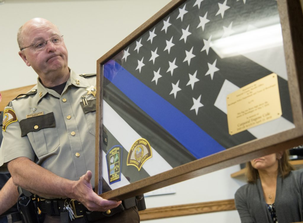 Somerset County Sheriff Dale Lancaster receives a memorial flag Tuesday in honor of the late Cpl. Eugene Cole, of the Somerset County Sheriff's Office, from Skowhegan police chief David Bucknam at the Skowhegan Municipal Building.