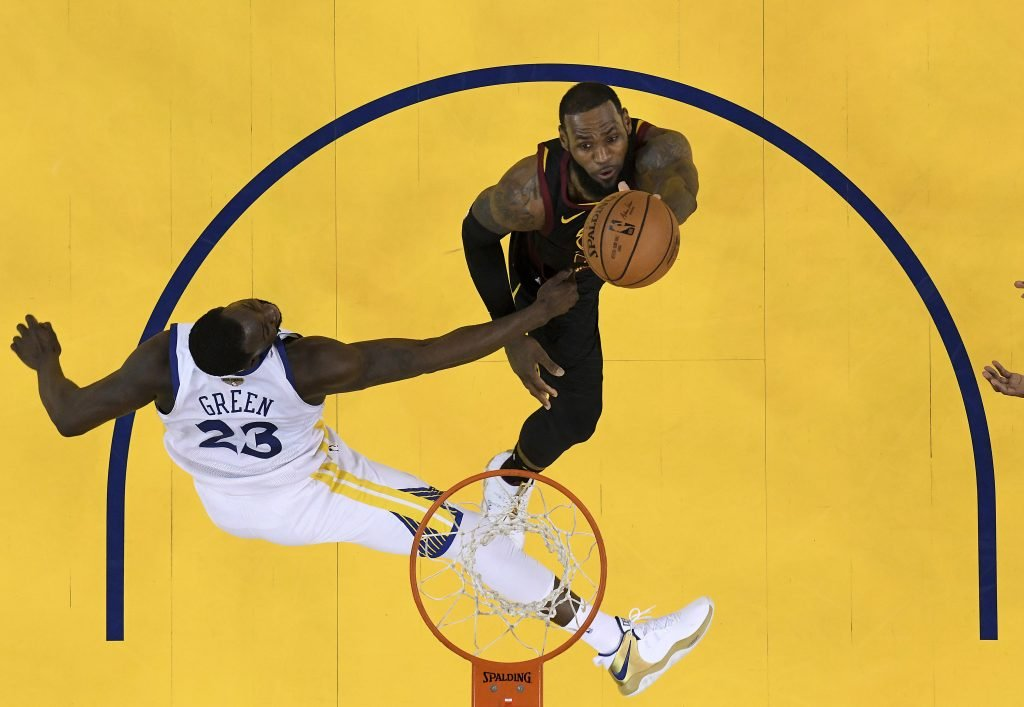 Cleveland Cavaliers forward LeBron James, top, shoots against Golden State Warriors forward Draymond Green during the second half of Game 1 of the NBA finals on Thursday in Oakland, Calif., Thursday. James scored 51 points but the Warriors won 124-114 in overtime.