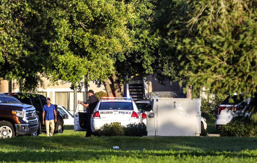 Police at the scene of the hostage standoff Monday in Orlando. Police said a man suspected of battering his girlfriend wounded a police officer late Sunday and barricaded himself inside an apartment with 4 young children. He later fatally shot the chlldren and himself.