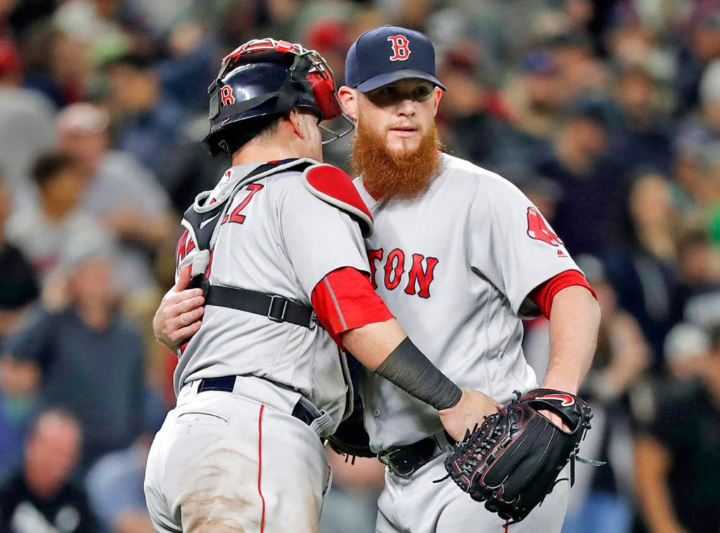 Red Sox closing pitcher Craig Kimbrel embraces catcher Christian Vazquez after the Red Sox defeated the Seattle Mariners 2-1.