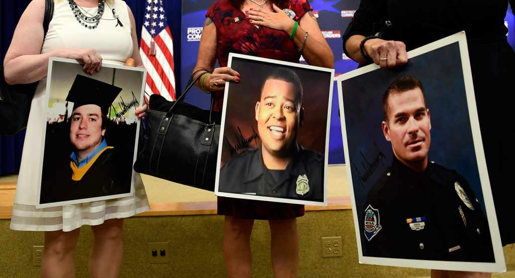 People holding photos of victims arrive for a White House event about crimes committed by undocumented immigrants, in Washington on Friday. President Trump arranged the session to push back against critics of his immigration policy.