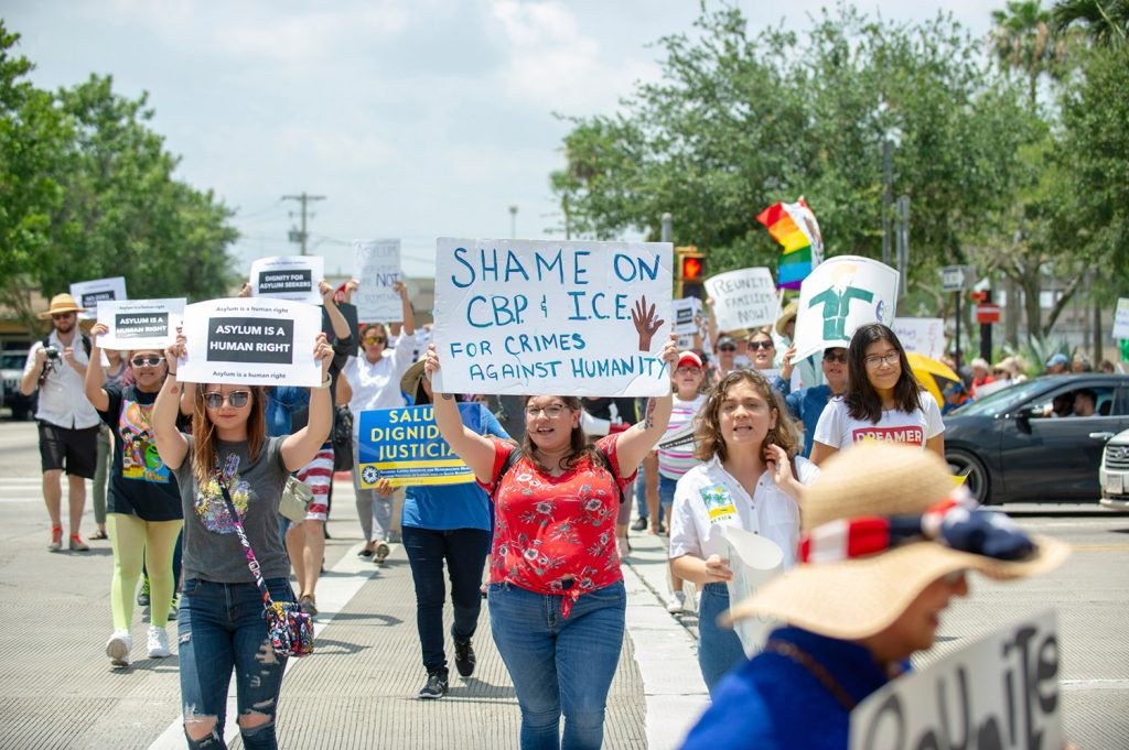 Demonstrators participate in an organized march Saturday near the Gateway International Bridge in downtown Brownsville, Texas, to protest the treatment of immigrants coming across the border.