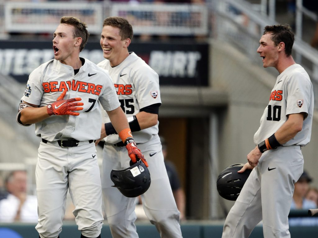Oregon State's Tyler Malone, 7, celebrates his three-run home run against Mississippi State in the third inning with Adley Rutschman, 35, and Michael Gretler in a College World Series elimination game Sunday in Omaha, Neb. Oregon State has won 109 of 127 games in the last two seasons, but feels it needs a victory in the CWS to validate its success.