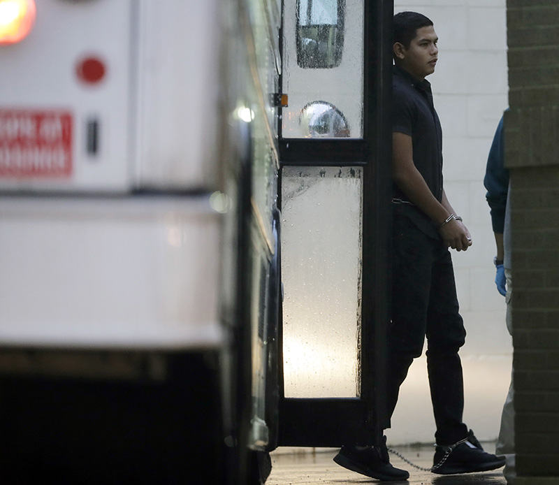 Immigrants in handcuffs and ankle chains arrive at the Federal Courthouse for hearings on Thursday in McAllen, Texas.