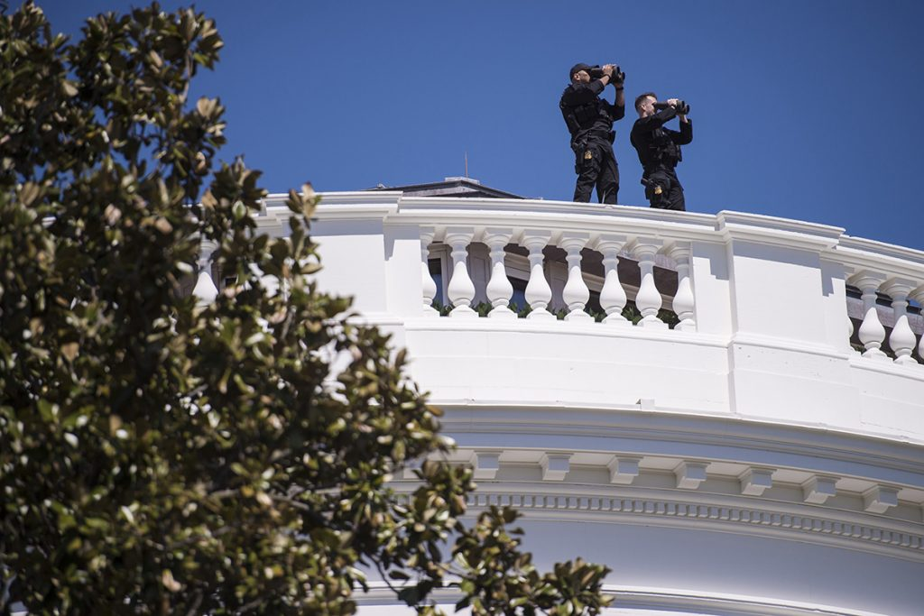 Members of the Secret Service patrol the top of the White House in 2015.