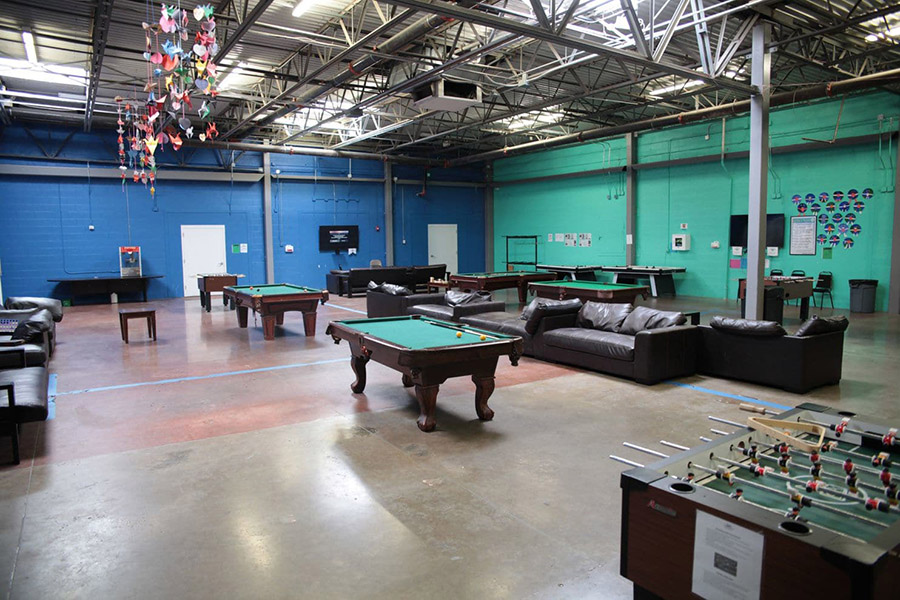 Children can play pool and foosball in a rec room at Casa Padre. Bedrooms are doorless, with walls reaching only halfway to a 20-foot-high industrial ceiling.