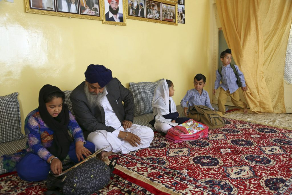 Avtar Singh Khalsa, a Sikh and longtime leader of the community, studies with his grandchildren at home, in Kabul, Afghanistan, on June 7.