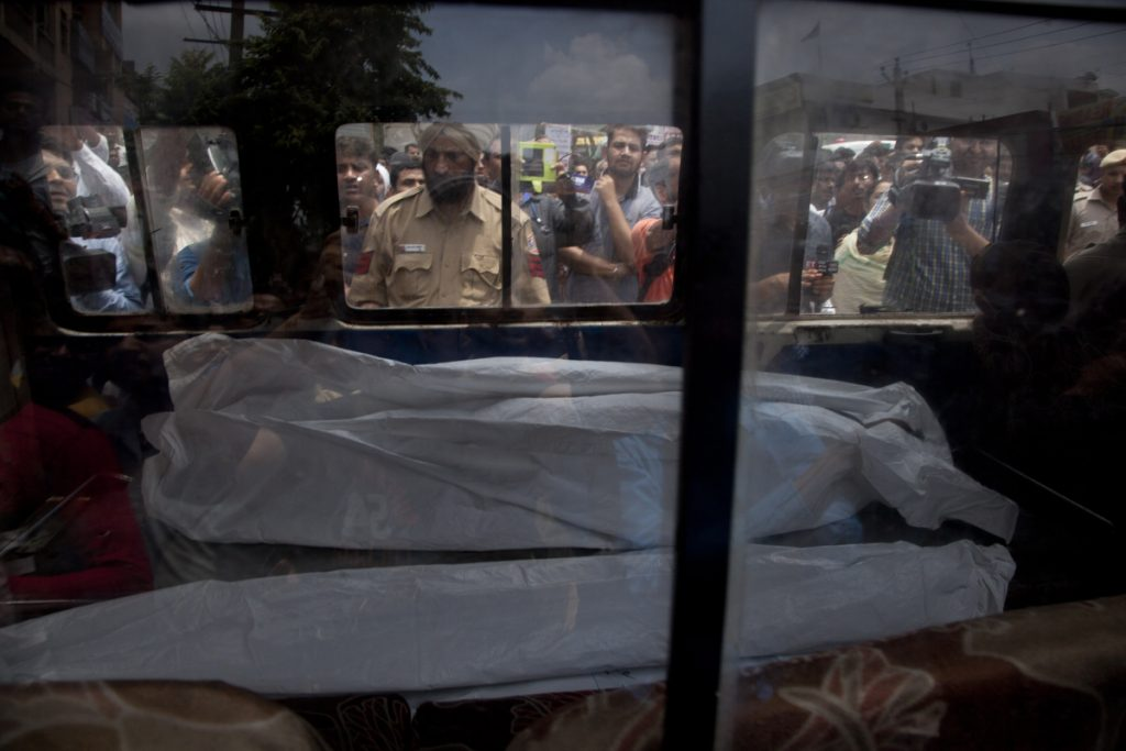 An ambulance carries one of the 11 bodies found in Burari village, New Delhi, India, on Sunday. Ten bodies, blindfolded by cotton and pieces of cloth, were found hanging from an iron grill used as a ventilator in the home's courtyard.