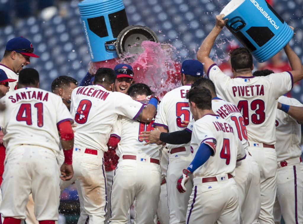 Andrew Knapp, center, is doused by his Phillies teammates at home plate after hitting a walkoff home run in the 13th inning against Washington on Sunday.