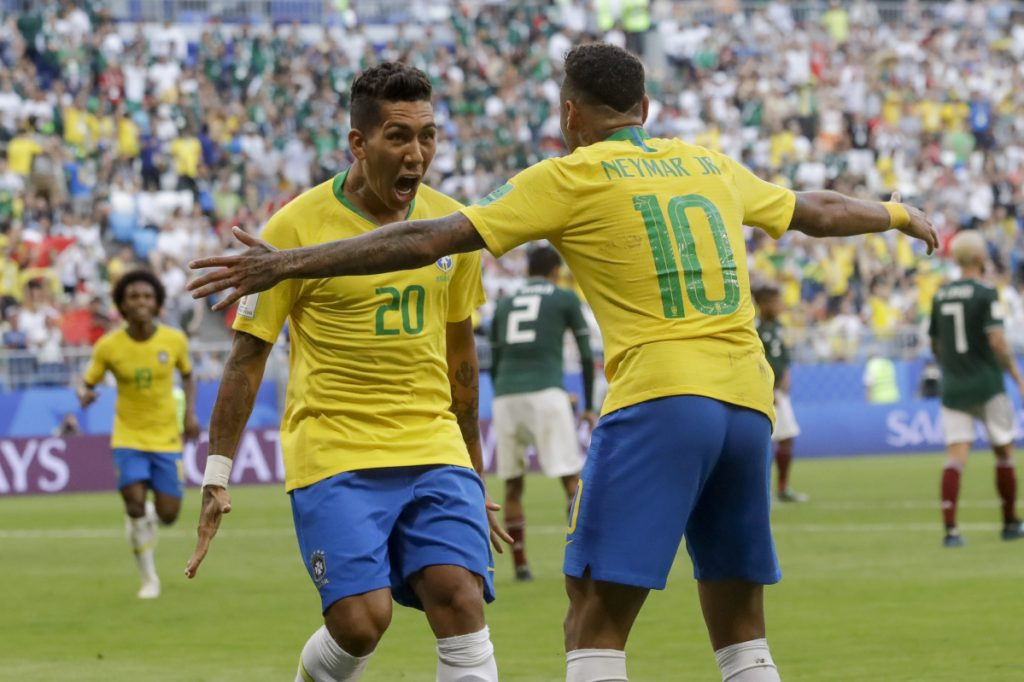 Brazil's Roberto Firmino, left, celebrates with Brazil's Neymar, right, after scoring his side's second goal against Mexico at the 2018 World Cup on Monday.