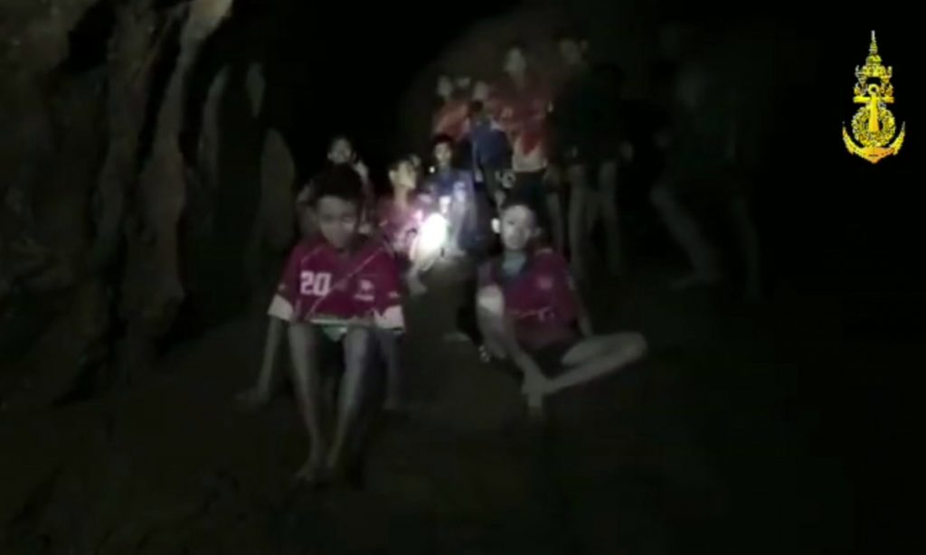 In this image taken from video provided by the Thai Navy Seal, the boys and their soccer coach sit in a cave in Chiang Rai in Thailand on Monday. The challenge now is to get them out.