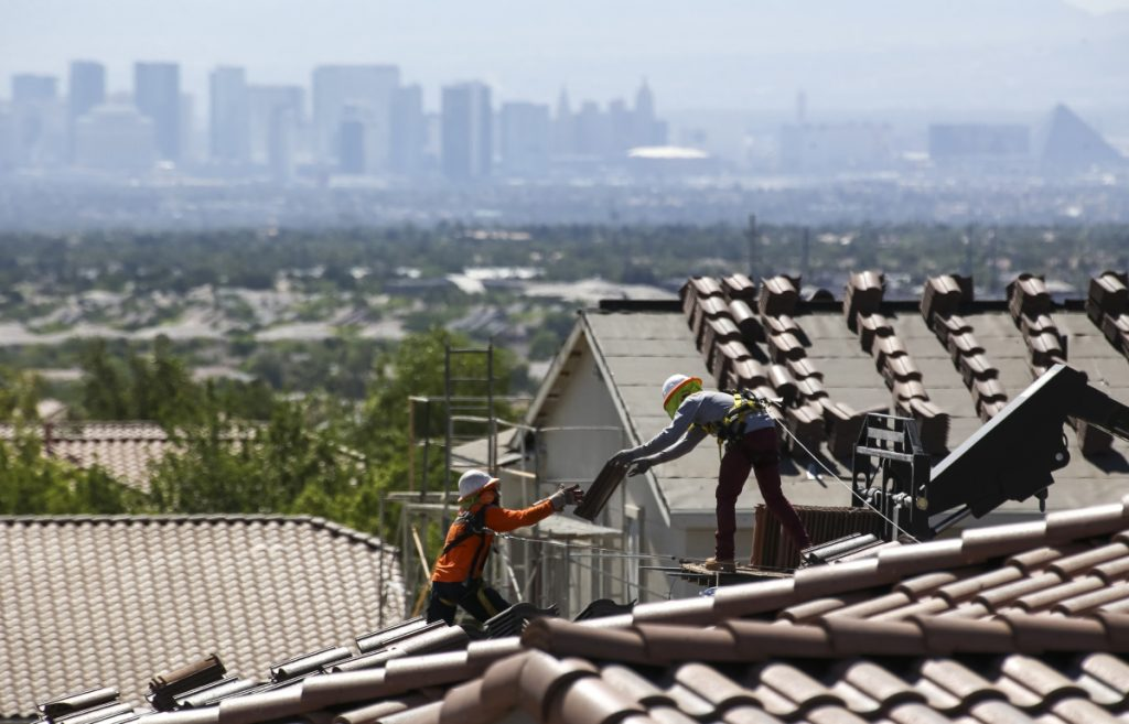 Construction workers set bundles of tile on the roof of an under-construction house in the master-planned community of Summerlin in Las Vegas. The Commerce Department reported Monday that U.S. construction spending rose in May.