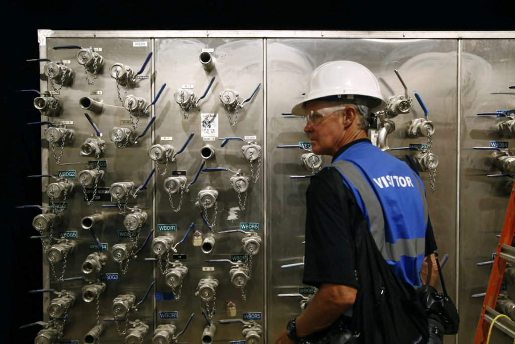 FILE- In this Wednesday, June 27, 2018 photo, a visitor walks past a valve box during a press tour of the Guinness Open Gate Brewery and Barrel House in Halethorpe, Md. On Monday, July 2, the Institute for Supply Management, a trade group of purchasing managers, issues its index of manufacturing activity for June. (AP Photo/Patrick Semansky, File)
