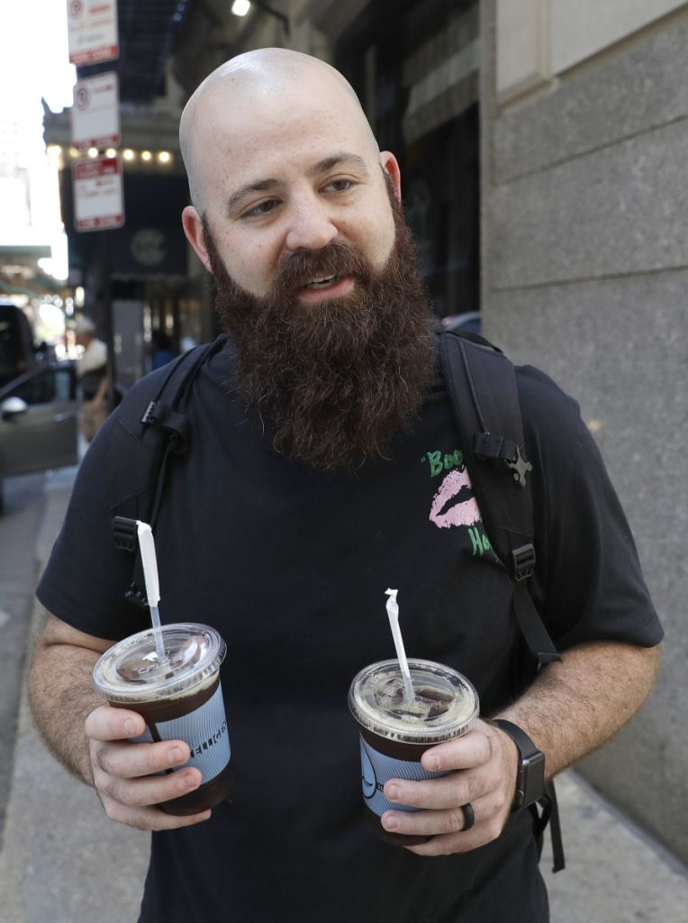 """Adam Taylor, a sound engineer from Las Vegas who bought iced coffees for friends Monday in Chicago: """"Coffee makes you happy"""" and is something to look forward to in the morning."""