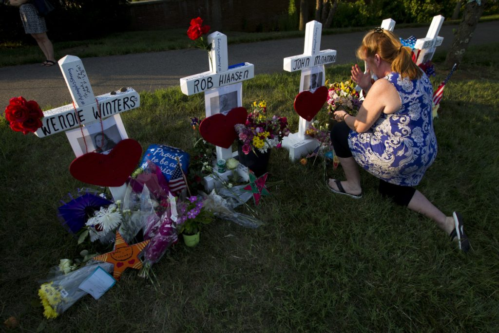Colleen Joseph prays over the crosses at a makeshift memorial at the scene outside The Capital Gazette newspaper in Annapolis, Md., on Sunday. Jarrod Ramos is charged with murder after police say he opened fire Thursday at the newspaper.