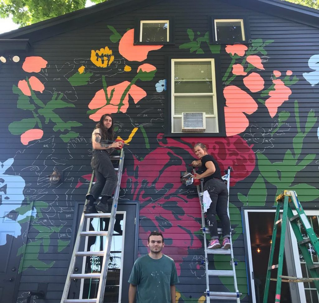 From left, Bee Marcellino, Baxter Koziol and Tessa O'Brien work on the new mural at Chaval.