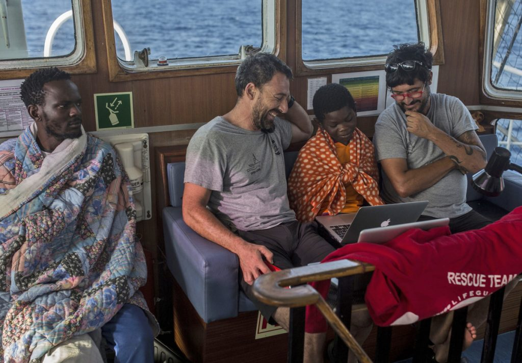 Guillermo Cañardo, chief of mission, and Marco Martinez Esteban, captain of the Open Arms boat, watch cartoons next to Khingsley Dokowada, 9, of Central African Republic, on Monday. The boat is carrying 60 migrants and will dock in Barcelona on Wednesday.
