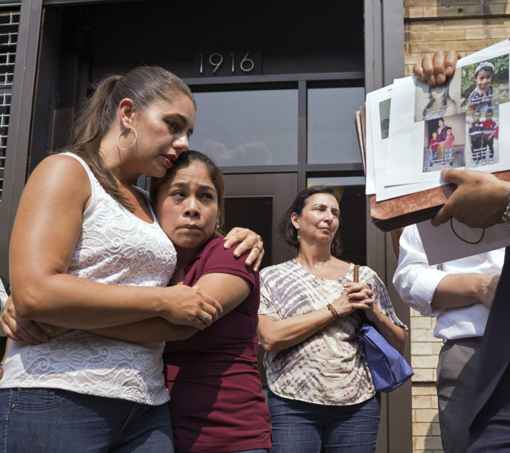 Yeni Gonzalez, a Guatemalan mother who was separated from her three children at the U.S.-Mexico border, center, is embraced by volunteer Janey Pearl, center left, during a news conference Tuesday in New York. Gonzalez saw her kids for the first time since mid-May.