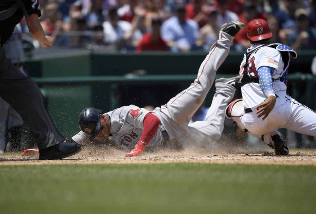 Boston's Rafael Devers, left, slides home past Washington catcher Pedro Severino to score on a sacrifice fly by Jackie Bradley Jr., during the seventh inning Wednesday's game in Washington.