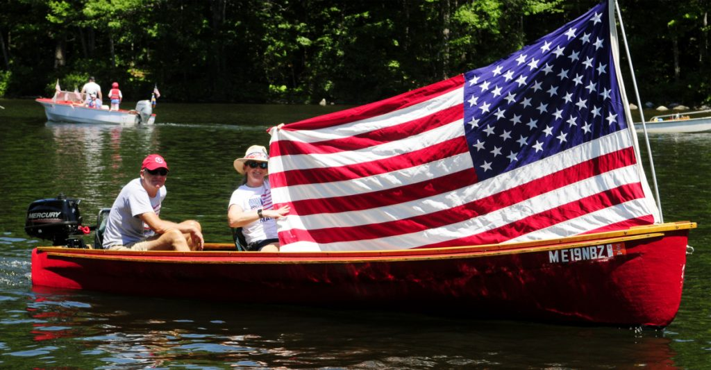 Boaters hold up a large American flag Wednesday during a boat parade on Mill Stream in Belgrade.