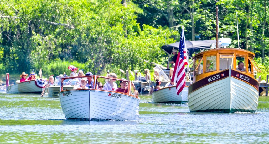 Classic wooden boats lead the parade Wednesday on Mill Stream in Belgrade. Boats started the parade on Great Pond and headed downstream into Belgrade Lakes village, then turned around and headed back out.