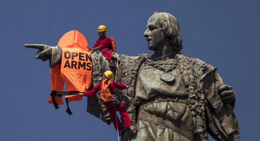 "Two activists climb from the Christopher Columbus statue after placing a vest with the words ""Open Arms"" on it in Barcelona on Wednesday,."