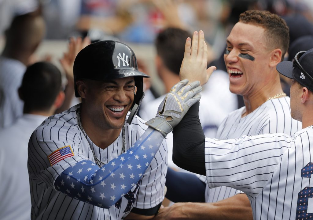 Giancarlo Stanton, left, celebrates in the dugout after smacking a three-run homer in the third inning Wednesday at Yankee Stadium. The Yankees added two more home runs in the game to beat the Braves, 6-2.