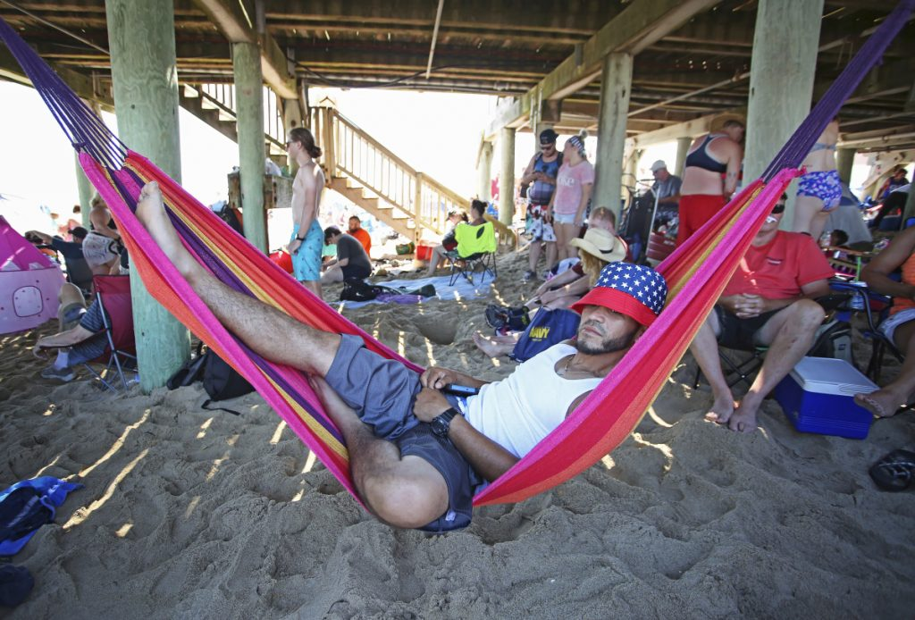 Antonio Seda, of Southbridge, Massachusetts, relaxes in a hammock he hung up under the pier at Old Orchard Beach on Wednesday, when Portland set a new record for the high temperature, hitting 93 degrees.