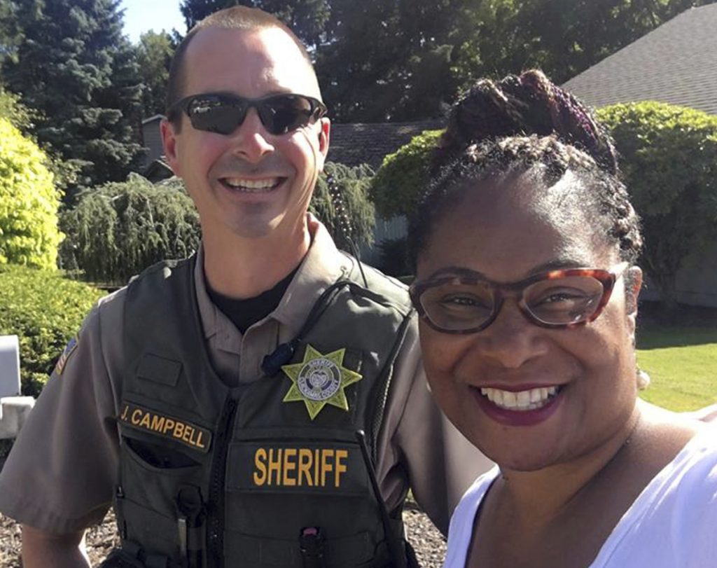 Oregon state Rep. Janelle Bynum poses with a Clackamas County sheriff's officer after he stopped her in Clackamas, Ore.