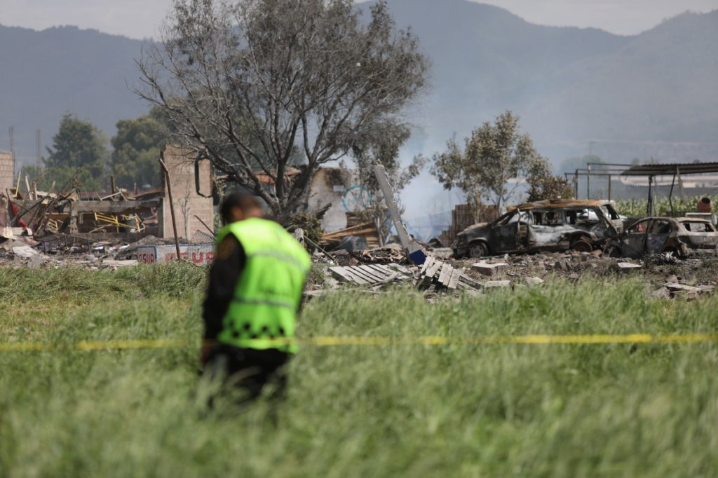 A series of four explosions destroyed four fireworks workshops in Tultepec, Mexico, on Thursday. Officials say the blasts were triggered by an explosion at an unauthorized operation that shot flammable material into the air and set off the subsequent locations. A police officer guards the perimeter around the wreckage of several fireworks workshops in Tultepec, Mexico, Thursday, July 5, 2018. More than a dozen people were killed and at least 40 injured  when a series of explosions ripped through fireworks workshops in a town just north of Mexico City. (Associated Press/Emilio Espejel)