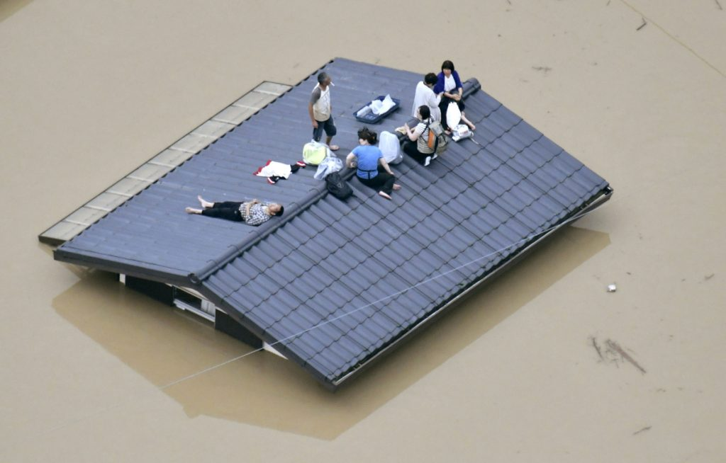 People wait to be rescued on the top of a house almost submerged in floodwaters caused by heavy rains in Kurashiki, Japan.