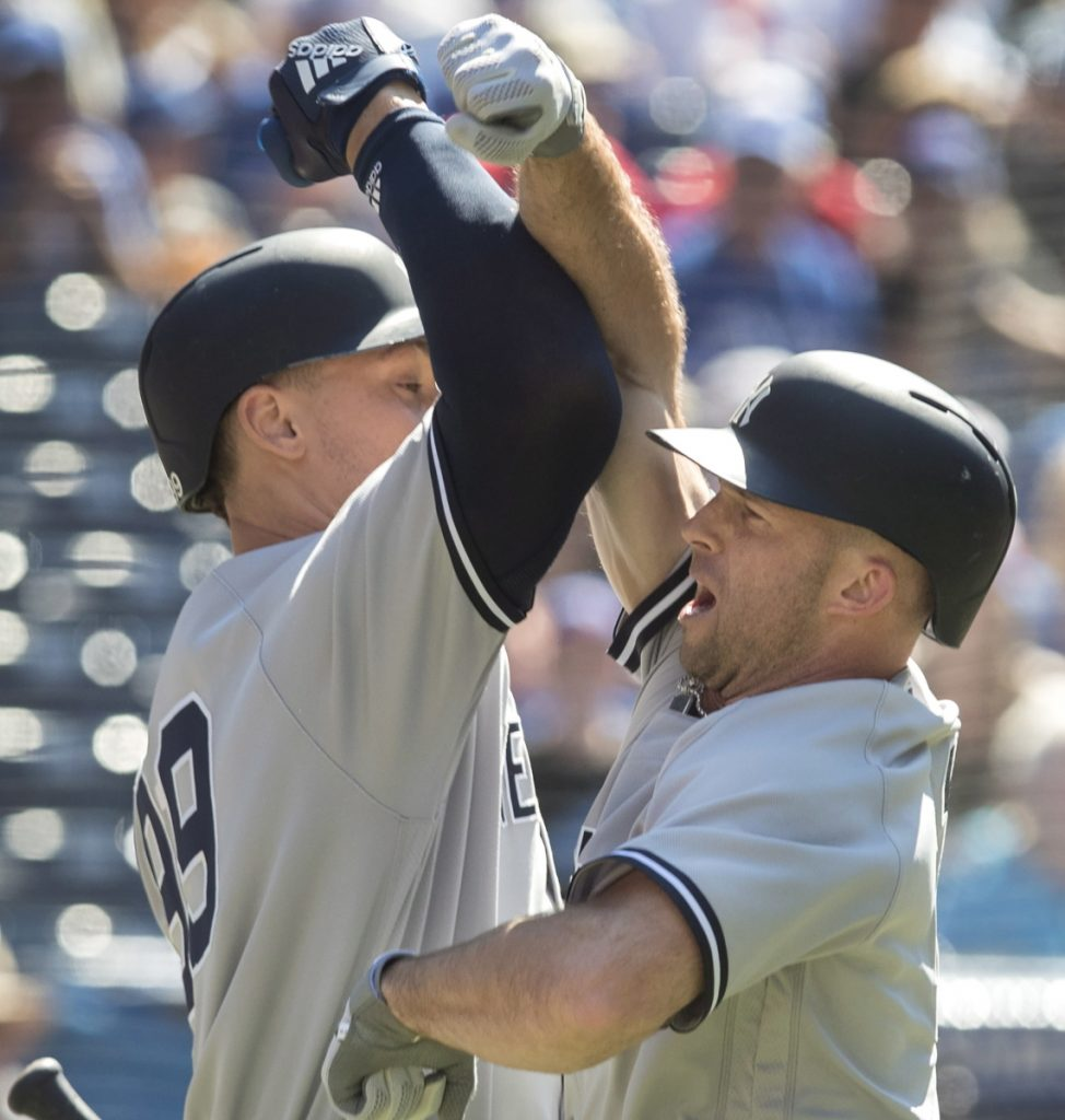 Brett Gardner, right, is greeted by Aaron Judge after homering on the first pitch Saturday. Judge followed with a homer and the New York Yankees beat the Toronto Blue Jays, 8-5.