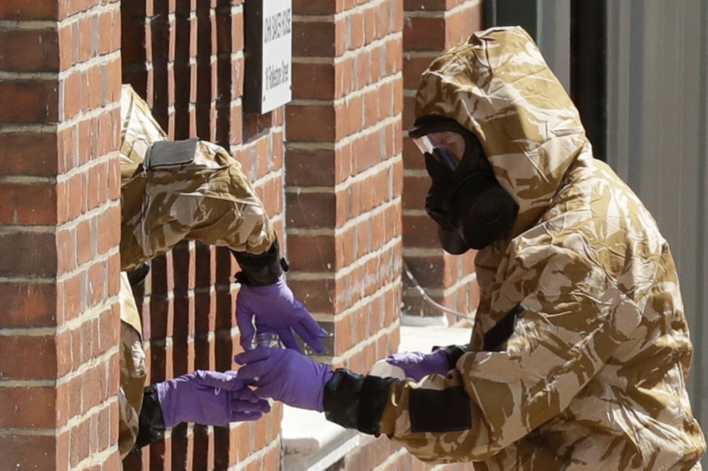 Police specialist team members in protective suits search the front doorway of the fenced-off John Baker House for homeless people in Salisbury, England, on Friday.