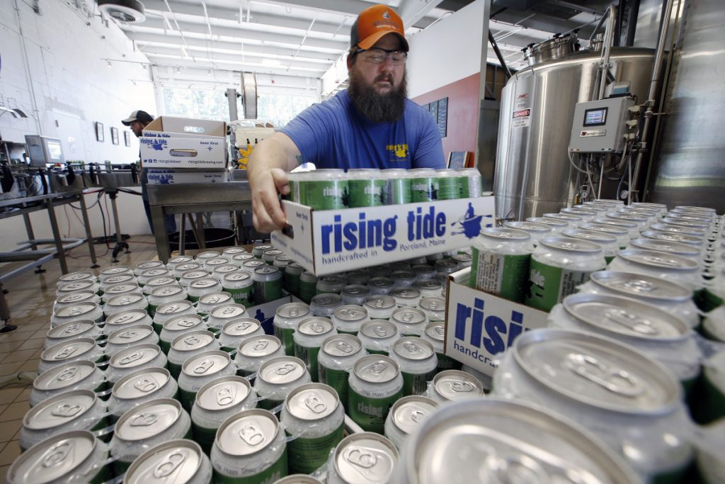Merritt Waldron stacks cases of the popular seasonal beer MITA. Breweries such as Rising Tide, which made 243 percent more beer in July than in February last year, have learned that cashing in on summer is the key to surviving the lean winter months.