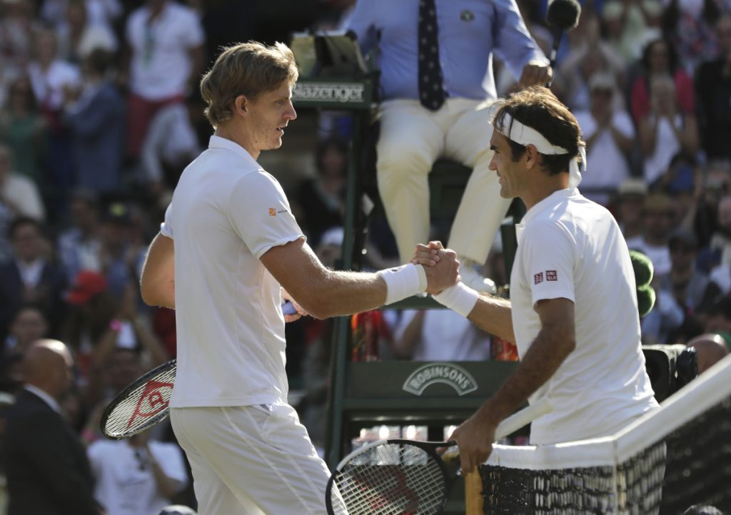 Kevin Anderson of South Africa, left, shakes hands with Switzerland's Roger Federer, after defeating him in their men's quarterfinals match at the Wimbledon Tennis Championships, in London, Wednesday July 11, 2018. (AP Photo/Ben Curtis)