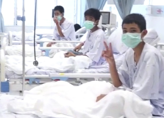 A video image shows three of the 12 rescued boys recovering in their hospital beds in Chiang Rai. Their parents have been allowed to see – but not touch – them.