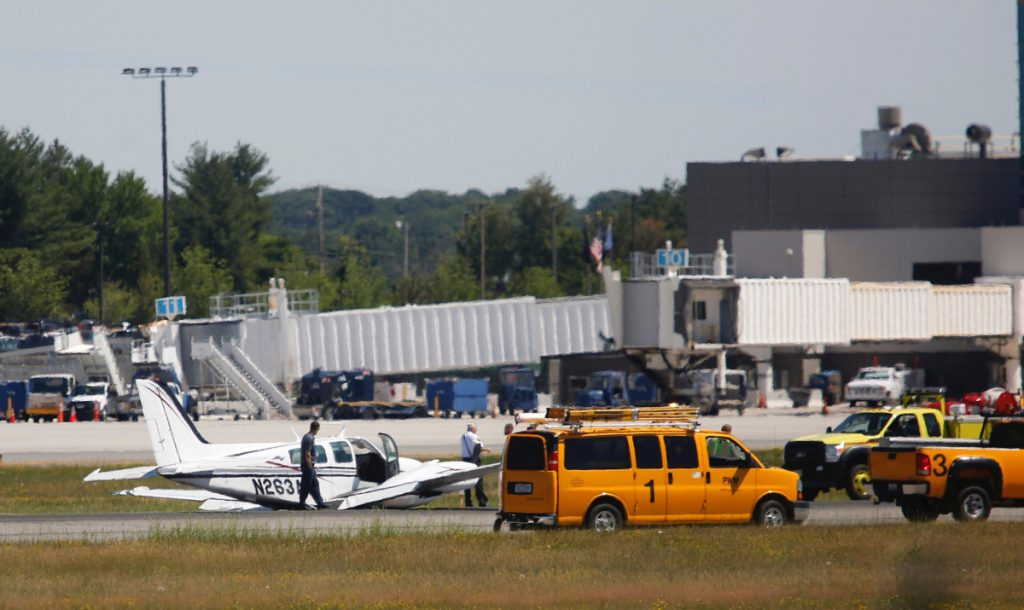 A twin-engine plane with two people aboard landed on its belly at Portland International Jetport on Thursday, causing all runways to close.
