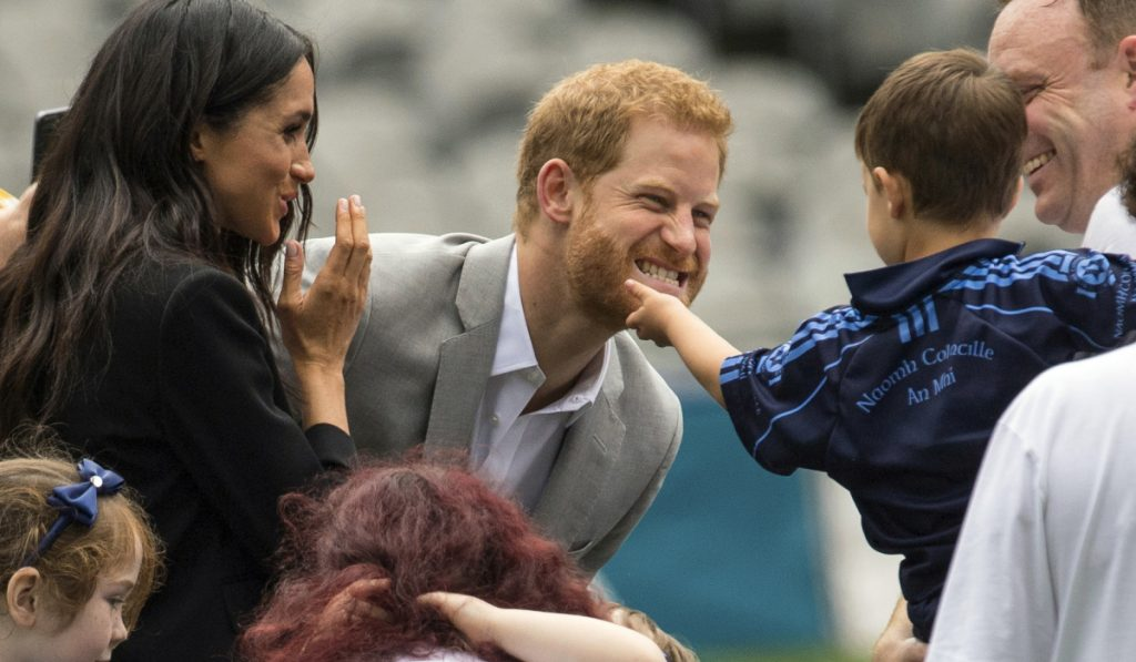 A boy strokes Prince Harry's beard as Meghan, the Duchess of Sussex, smiles in Dublin, Ireland, Wednesday.