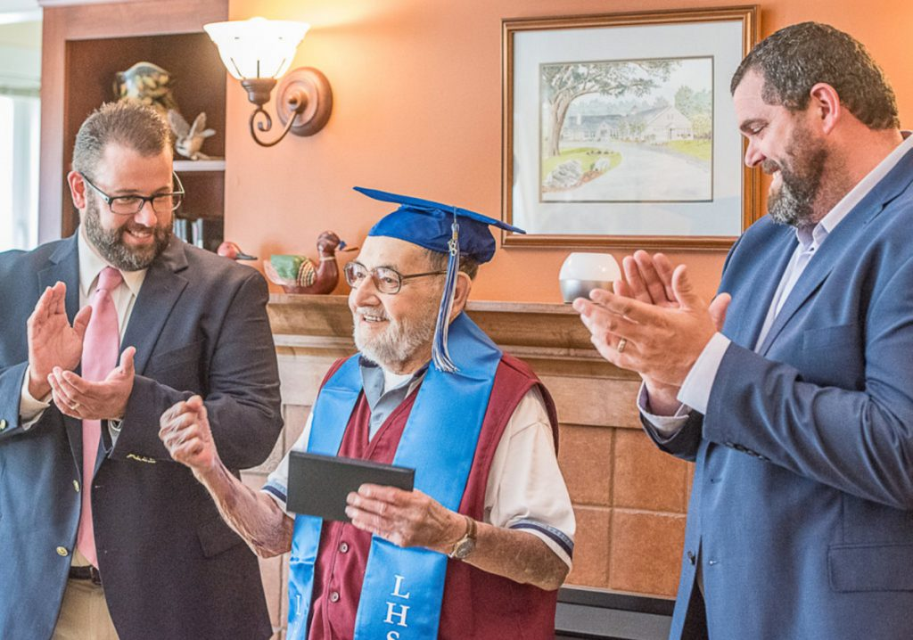 Hospice volunteer Leo Savard, 86, pumps his fist Thursday after getting his Lewiston High School diploma. Presenting the diploma are Assistant Principal Jay Dufour, left, and Principal Jake Langlais.