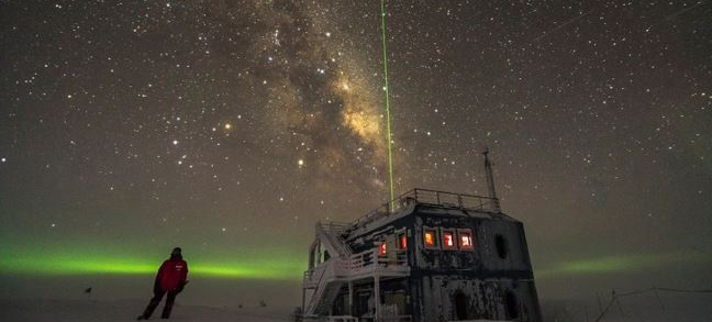 The IceCube lab lit by stars and the southern lights.