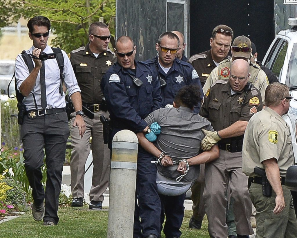 Activists are removed from a building in Centerville, Ore., on Thursday after they protested a private prison company that has contracts with the government to hold immigrants. escorted out of a building where they staged a protest against a private prison company with contracts to hold immigrants on Thursday, July 12, 2018, at the headquarters of Management and Training Corporation in Centerville, Ore.