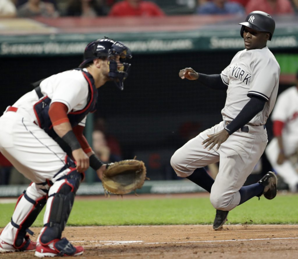 Didi Gregorius of the Yankees scores the go-ahead run on a double by Aaron Hicks as Indians catcher Yan Gomes waits for the throw during the eighth inning Thursday in Cleveland. New York went on to a 7-4 victory.