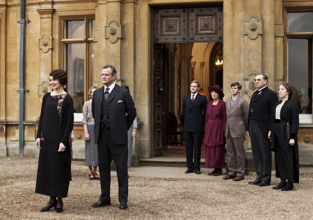 "This undated publicity photo provided by PBS shows, from left, Elizabeth McGovern as Lady Grantham, Hugh Bonneville as Lord Grantham, Dan Stevens as Matthew Crawley, Penelope Wilton as Isobel Crawley, Allen Leech as Tom Branson, Jim Carter as Mr. Carson, and Phyllis Logan as Mrs. Hughes, from the TV series, ""Downton Abbey."" Focus Features said Friday, July 13, that it will this summer begin production on a ""Downton"" film that will reunite the Crawley family on the big screen. Series creator Julian Fellowes wrote the screenplay and will produce. (AP Photo/PBS, Carnival Film & Television Limited 2012 for MASTERPIECE, Nick Briggs)"