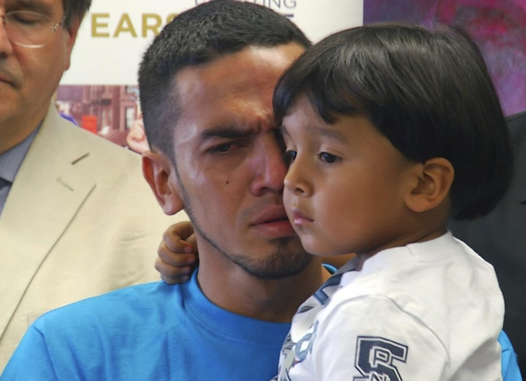 In this image taken from video, Javier Garrido Martinez holds his 4-year-old son Wednesday after they were reunited, during a news conference in New York. The Trump administration faces another deadline this month to reunify families separated at the border.