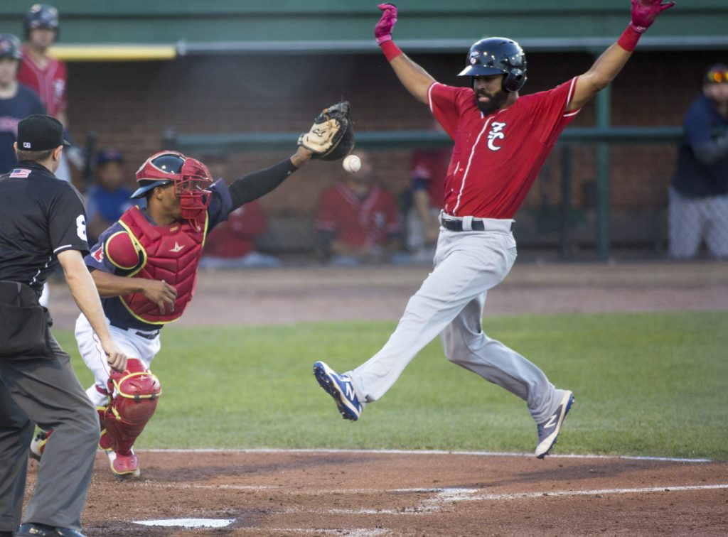 Catcher Jhon Nunez of the Portland Sea Dogs attempts to hold the ball as Dalton Pompey of the New Hampshire Fisher Cats prepares to score Friday night during the fourth inning of New Hampshire's 5-3 victory at Hadlock Field.